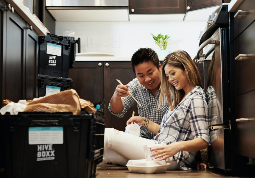 couple sitting on floor in kitchen eating takeout
